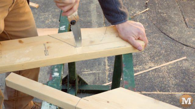 firewood cutting jig - pocket hand saw handles on sawhorse