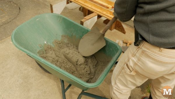 Mix concrete with cold water in wheelbarrow - man about tools cast form mold concrete garden boxes