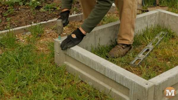 Pound in rebar to secure corners - man about tools cast form mold concrete garden boxes