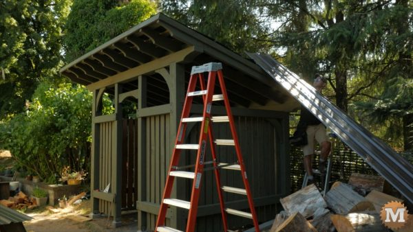 Sliding the first roof panel into place - Timber Frame Firewood Shed