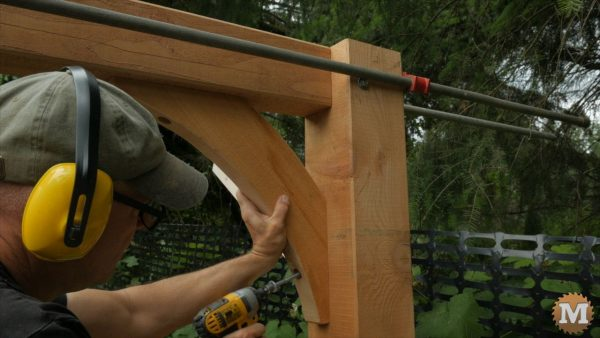 Hold brace in place, drill, then run in long lag bolt with impact driver - Post and Beam Woodshed