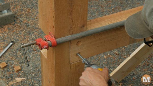 Secure with a long bar clamp, then drill and run in some lag bolts into post - Timber Frame Shed