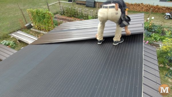 Lining up and screwing tin roof panels