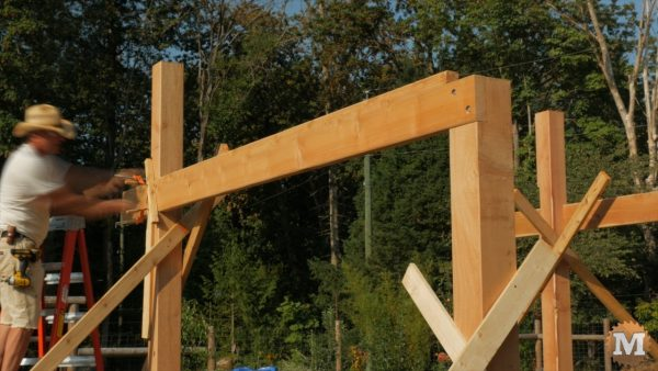 Installing first side girt with lag bolts - Timber Frame Pavilion