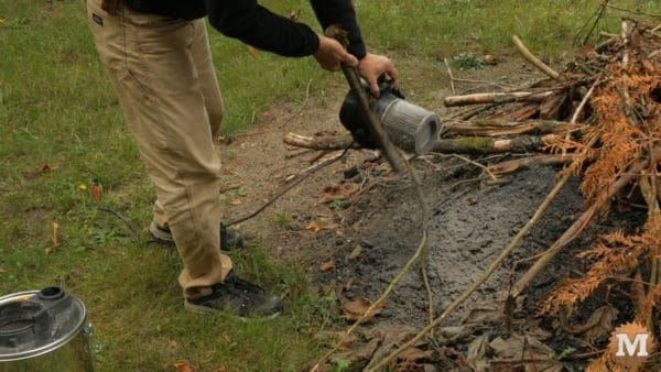 Gently tapping the filters with a stick to clean off ash and creosote