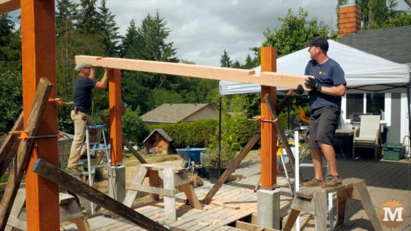 lifting a beam of the Three Gable Timber Frame style Pavilion into place