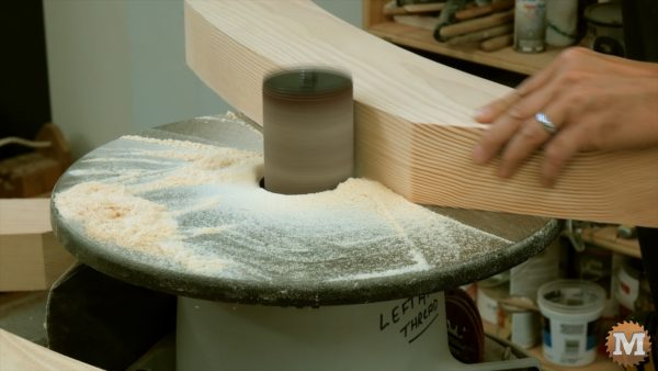 sanding the curved corner braces for the Three Gable Timber Frame style Pavilion from fir
