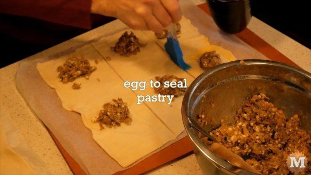 Brushing on egg mixture to seal the wild mushroom tart pastry