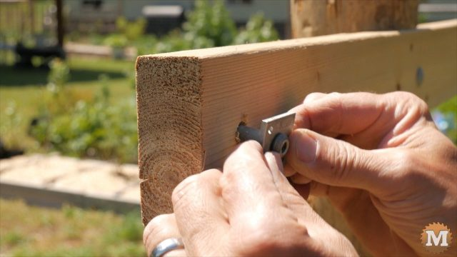 Wire vise being inserted into hole in trellis cross member